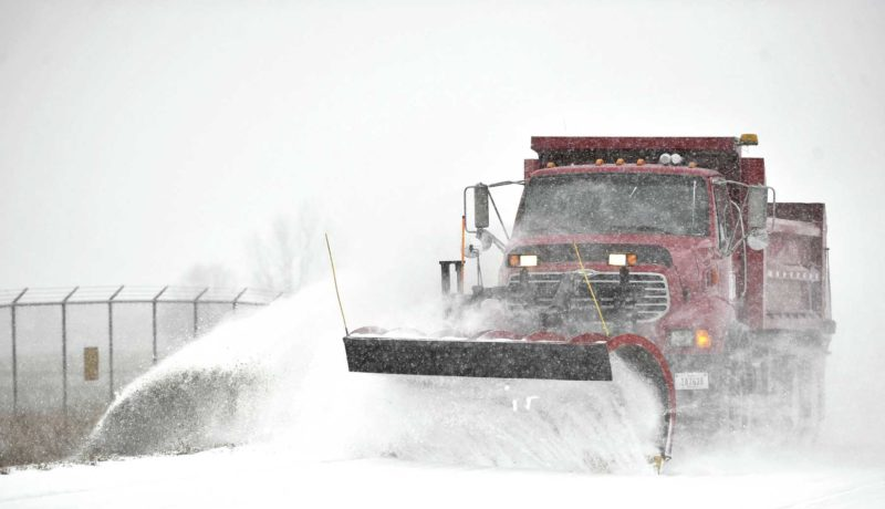 -Messenger photo by Hans Madsen  A Webster County Highway Department plow truck sends a spray of freshly fallen snow into the ditch along Orchard Road west of the Fort Dodge Regional Airport during Saturday morning's snow fall.