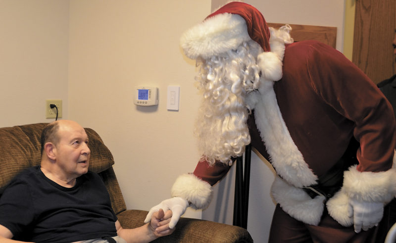 -Messenger photo by Chad Thompson  Dave Martens, a resident at the Marian Home in Fort Dodge, receives a Christmas greeting from Santa Claus Sunday afternoon. The Fort Dodge Noon Sertoma with help from the Young Professionals delivered plants as gifts to four nursing homes in Fort Dodge.