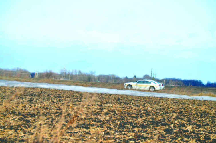 -Messenger photo by Peter Kaspari Two Webster County sheriff's deputies are parked in a field where a man was found dead Monday morning.