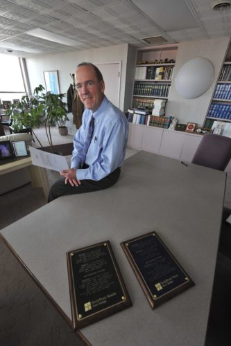 -Messenger photo by Hans Madsen  Fort Dodge attorney Kurt Pittner poses in his office Friday with several plaques he was given in recognition of his years of service on the Trinity Regional Medical Center and UnityPoint Health — Fort Dodge board. Pittner is retiring from the position.