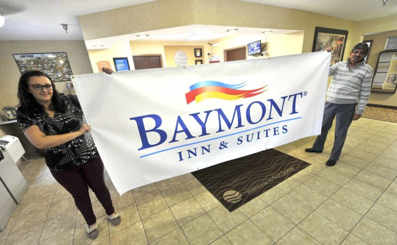-Messenger photo by Hans Madsen  Paresh Bhatt, at right, who owns what will soon be named the Baymont Inn & Suites, and Whitney Faulkner, hotel manager, hold up a banner that will be used to help rebrand the property as the Baymont Inn & Suites. The hotel is at 2938 Fifth Ave. S. on the city's Corridor of Commerce.