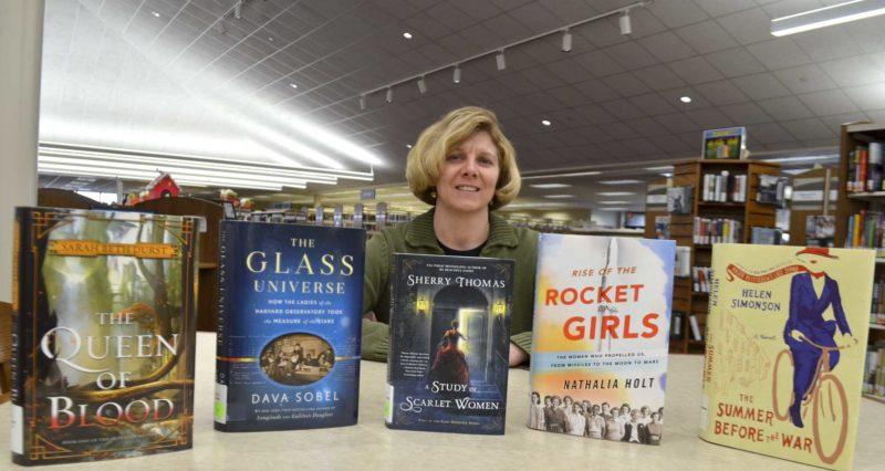 -Messenger photo by Peter Kaspari Laurie Hotz, director of youth services at the Fort Dodge Public Library, arranges some of the books she recommends for young readers this winter.