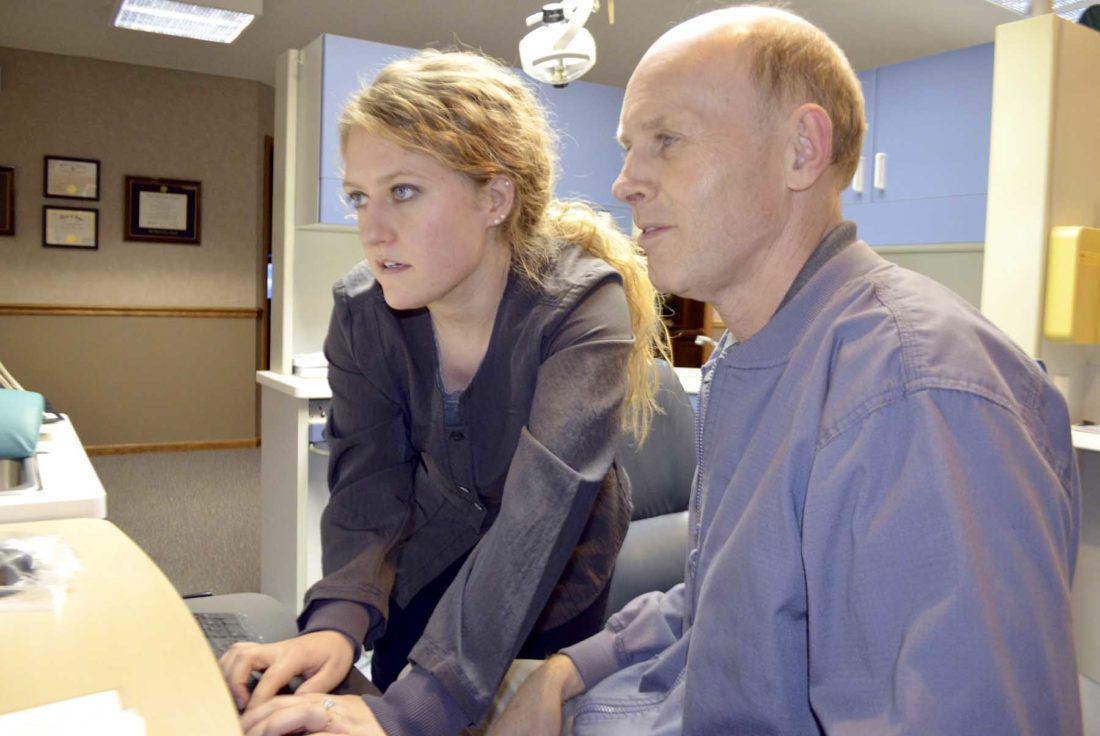 -Messenger photo by Chad Thompson  Dr. Jim Knight, front, and his daughter, Dr. Amy Seehusen, review X-rays at the office recently.