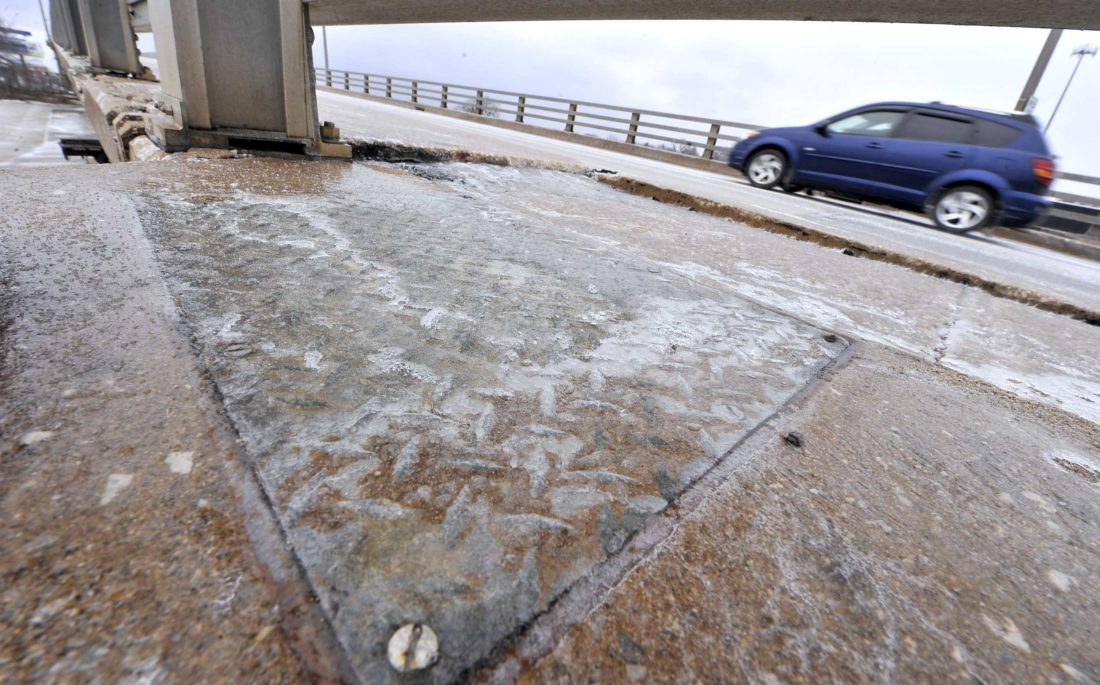 -Messenger photo by Hans Madsen  A motorist makes their way up the Veterans Memorial Bridge on First Avenue South Tuesday afternoon as a layer of ice continues to coat the sidewalk and railings after the early morning freezing rain.