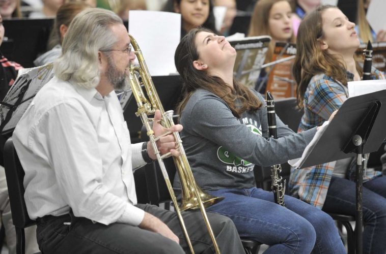 -Messenger photo by Hans Madsen  AAlex Tiernan, 11, reacts to the next difficult piece of music Saturday afternoon as she rehearses with the Sixth Grade Karl King Honor Band at St. Edmond Catholic School. Dan Cassady, left, the former director of bands at St. Edmond, sat in for a few minutes to prank his friend Kathy Yoakam, of Humboldt, who was directing the group.
