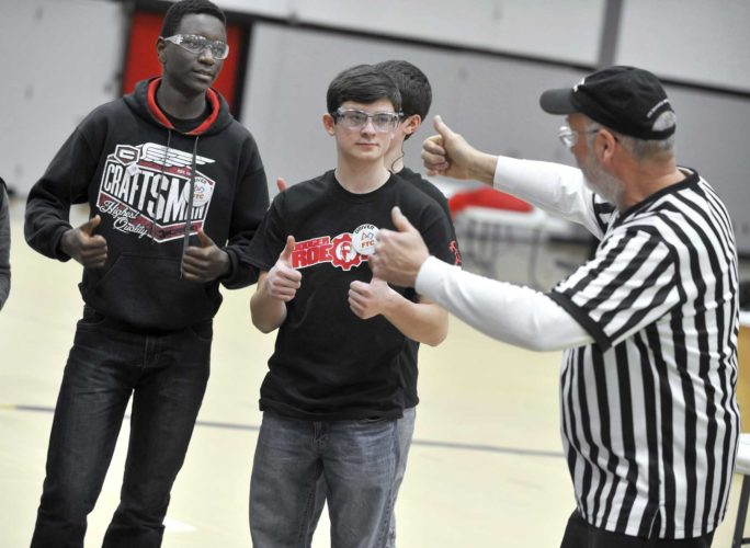 -Messenger photo by Hans Madsen  Dave Karisa, 16, of Fort Dodge, at left, along with his Robotics teammate Daniel Winkler, 16, are encoured to give a thumbs up by referee Dale Herzberg, of Des Moines, at the start of the First Tech Challenge Robotics League Championship at Fort Dodge Senior High.