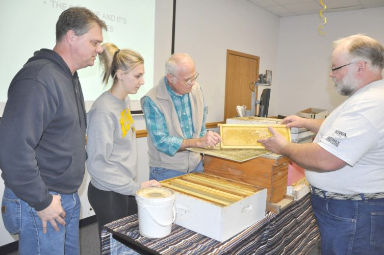 -Messenger photo by Larry Kershner Instructor Roy Kraft, right, discusses a beehive tray with, from left, Kyle Welander and his daughter Raegan Welander, both of Rockwell City; and David Welander, of Pomeroy. The elder Welander has been keeping bees for four years. His granddaughter Raegan said she wants to start beekeeping as an FFA supervised agricultural experience project.