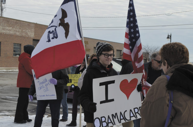 -Messenger photo by Chad Thompson  Liam Conrad, 17, of Fort Dodge, is shown here with a sign showing his support for the Affordable Care Act during a rally by the Webster County Democrats at City Square Park in Fort Dodge Sunday afternoon.