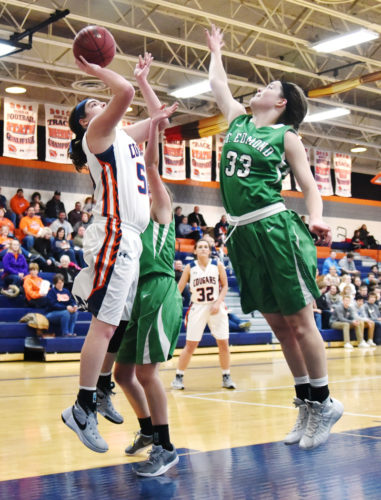 Messenger photo by Britt Kudla  Erin Flattery of St. Edmond tries to block a shot by Manson Northwest Webster's Becca Krueger last week in Manson.