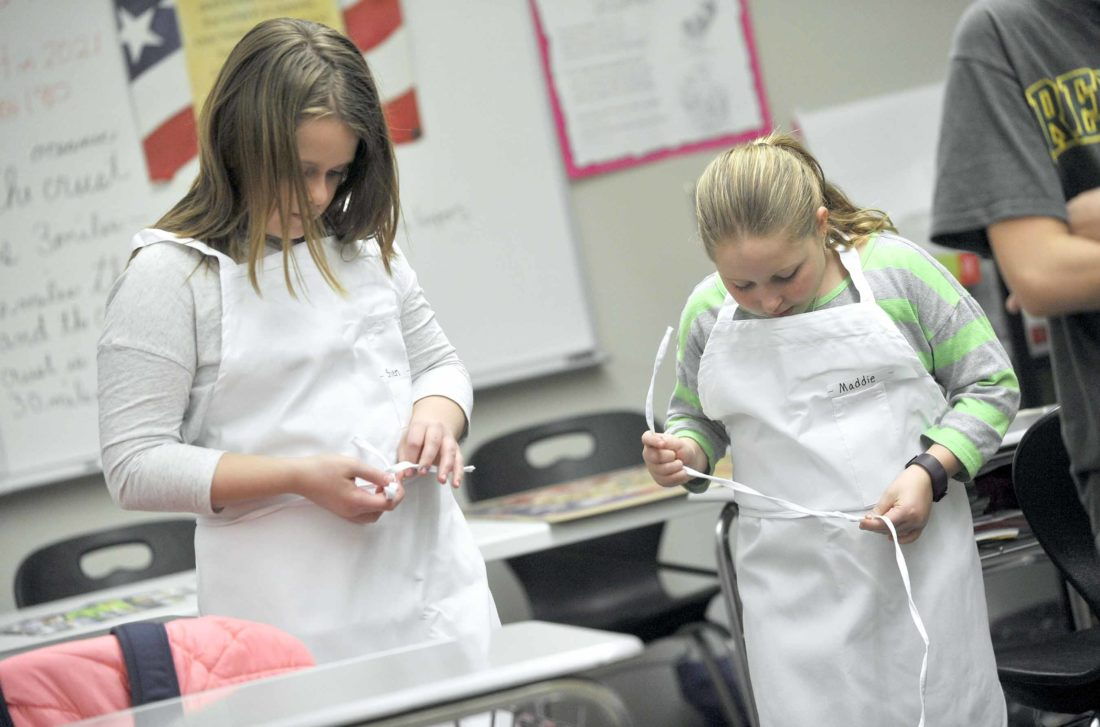 -Messenger photo by Hans Madsen  Shylen Hicks, 10, at left, along with Maddie Lee, 10, work on getting their aprons tied and adjusted Thursday afternoon during the first winter meeting of the Quick Fixin' Young Chefs Club at the Fort Dodge Middle School. The club members made a chicken enchilada dip that earned high ratings when it was done.
