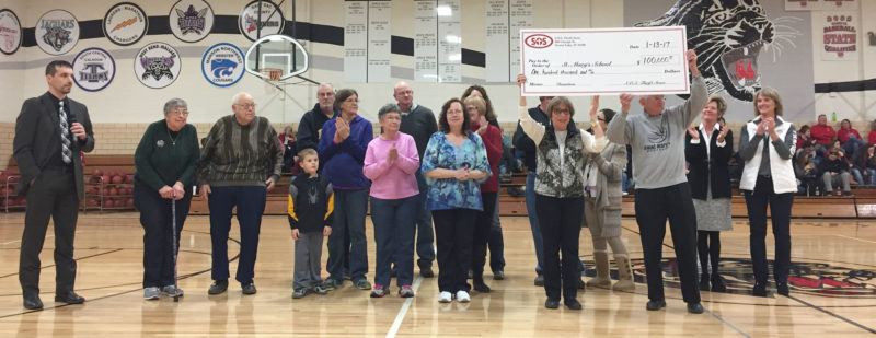 The Storm Lake SOS Thrift Store weekday volunteers and board presented a check for $100,000 to St. Mary's administration at last Friday's Storm Lake St. Mary's High School homecoming game. The contribution is raised through sales at the local thrift store which is just north of St. Mary's Church, run by volunteers. Pictured from left are board Treasurer Nick Landgraf , Bill and Carol Peters of Remsen, Roger and Caron Iehl, Donna Pishek, Jeff Kestel, Connie Hoye, Pat Miller (partially hidden), Lisa Hurd (partially hidden), store manager Shirley Kelley and longtime board member Wayne Andrews holding check, board chair Marty Broich and board member Maggie Reyes (both partially hidden) and 6-12 principal Cindy Cone and PreK-5 Principal Diane Jones.