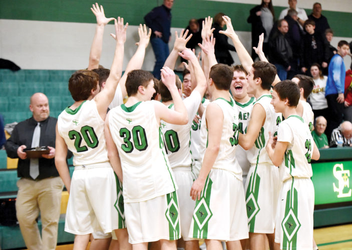 Messenger photo by Britt Kudla  St. Edmond players celebrate head coach Adolph Kochendorfer's 500th career victory in the Gael gym on Saturday.