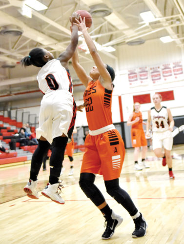Messenger photo by Britt Kudla  Shariah Smith of Fort Dodge, who is 4-foot-9, blocks a shot attempt by 5-9 Ames forward Teagan Lipsey on Monday in the Dodger gym. For more photos, please visit CU.messengernews.net