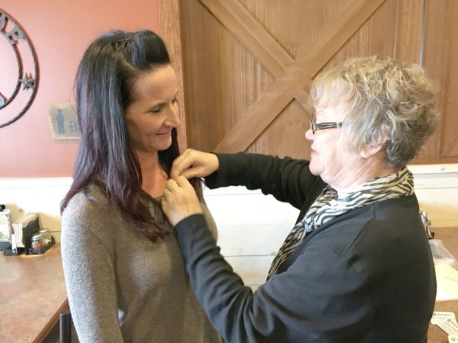 Fort Dodge Kiwanis President Carolyn Chelleen pins the newest member, Erica Loerts Loerts is the daughter of Kiwanis International President Jane Erickson. Erickson joined the Fort Dodge Kiwanis Club and was club president, district governor and several other offices prior to being elected president of  Kiwanis International. Loerts is a smoking cessation and prevention specialist at the Webster County Health Department.