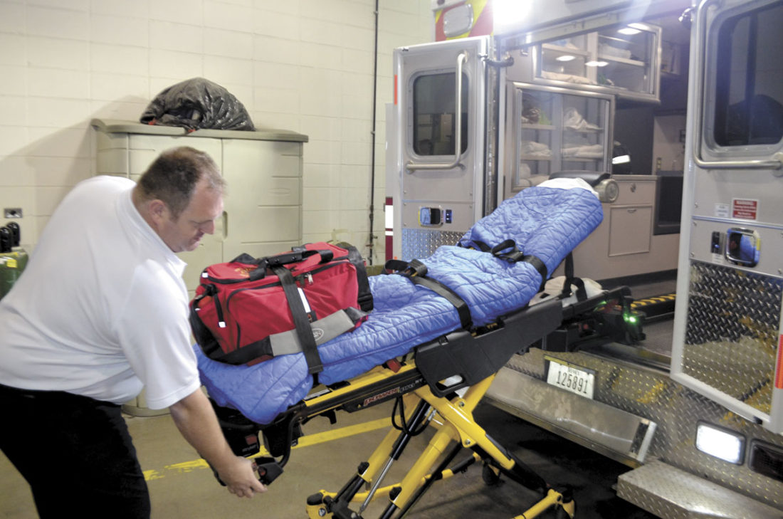 -Messenger photo by Bill Shea  Assistant Fire Chief Lenny Sanders activates an automatic lift system that will load a cot into the Fort Dodge Fire Department's new ambulance. Sanders said using the system eliminates the possibility that firefighters will sustain back injuries lifting the cot into the ambulance.