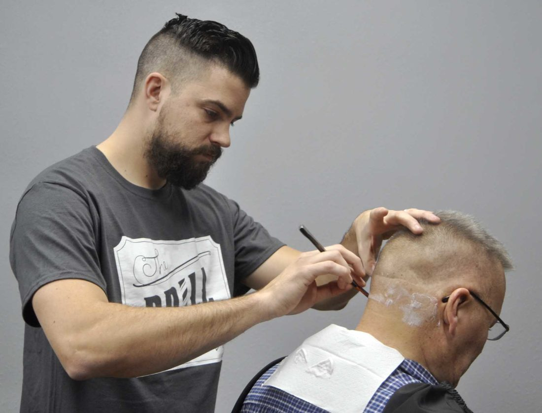 -Messenger photo by Chad Thompson  Ron Hedeen, of Fort Dodge, gets a straight razor shave from Phil DeCastro at The Drill Barbershop in Fort Dodge recently.