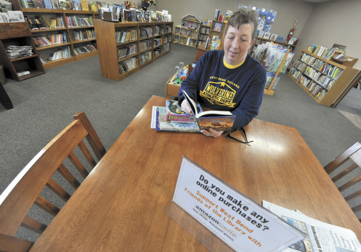 -Messenger photo by Hans Madsen  West Bend Public Library Executive Director Lisa Riesenberg takes a glance at one of the young sdult books available in her library.