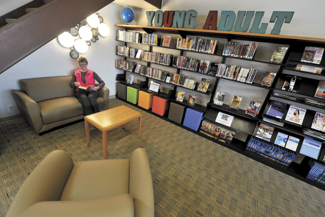 -Messenger photo by Hans Madsen  Manson Public Library director Laura Koons enjoys the newly remodeled Young Adult section. New shelving, lights and comfortable furniture complete the area.