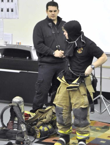-Messenger photo by Peter Kaspari  Fort Dodge Firefighter Devon Schuster, right, puts on his turnout gear as Firefighter Randy Schilling, left, explains how the gear works. The firefighters were at Duncombe Elementary School Tuesday afternoon to teach kindergarten students about their jobs.