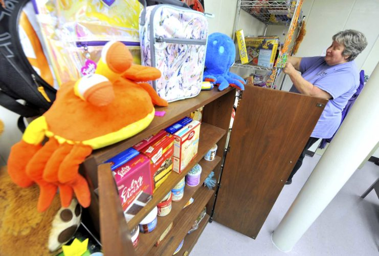 -Messenger photo by Hans Madsen  Bev Verschoor, an outreach specialist with Upper Des Moines Opportunity, looks over some of the gifts, cake making supplies and other items available in the birthday room.