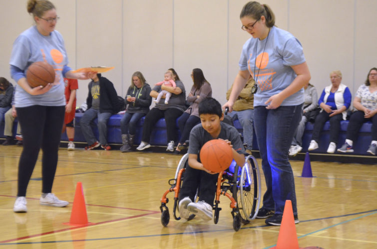 -Messenger photo by Joe Sutter  Angel Gervacio, a fourth-grader from Cooper Elementary School, gets some help from volunteer Hannah Gebers in the 10-meter basketball dribble event. Gervacio turned heads all morning with the bright color-changing lights on his wheels.