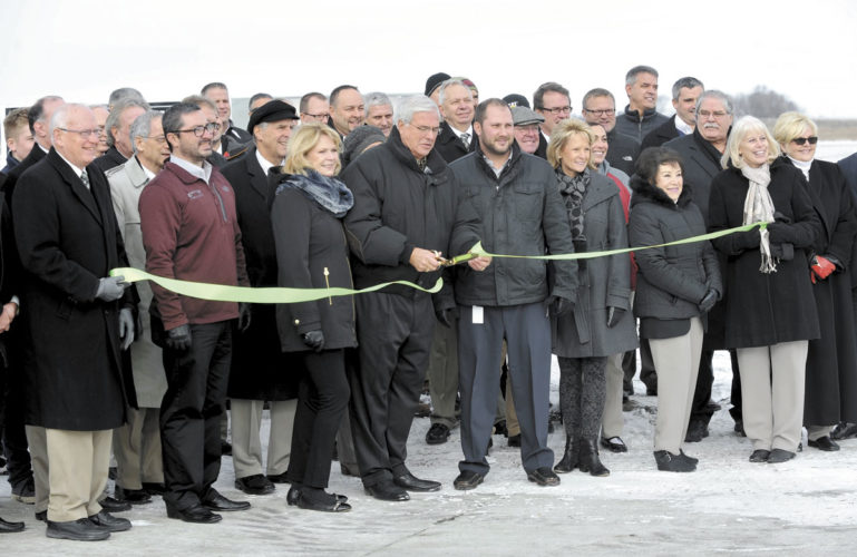 -Messenger photo by Hans Madsen  Decker Truck Line Inc. Chairman of the Board Don Decker, center, cuts the ribbon for the Decker Development Park on the east side of Fort Dodge. The site has over 100 acres of land available for commercial development.