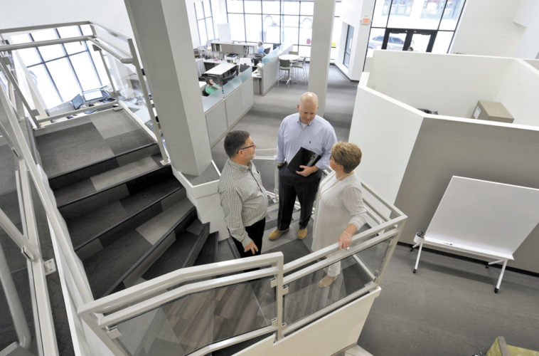 -Messenger photo by Hans Madsen  Kingsgate Insurance President Ed Smith, at left, stops to chat with vice presidents Ryan Smith and Denise Smith on the landing of the stairs leading to their offices. The agency moved into remodeled offices at 924 Central Ave. in downtown Fort Dodge in 2016.