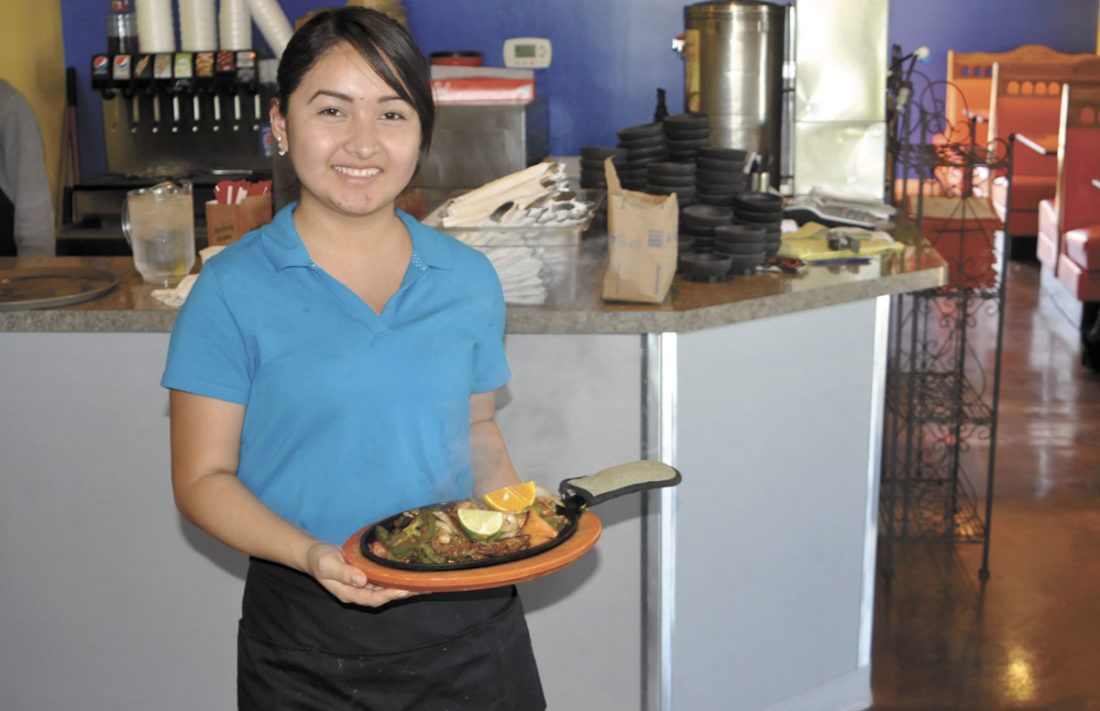 -Messenger photo by Chad Thompson  Paulina Galvan, a waitress at Lomita's Mexican Restuarant, shows off a specialty dish at the restaurant's new location on Fifth Avenue South.