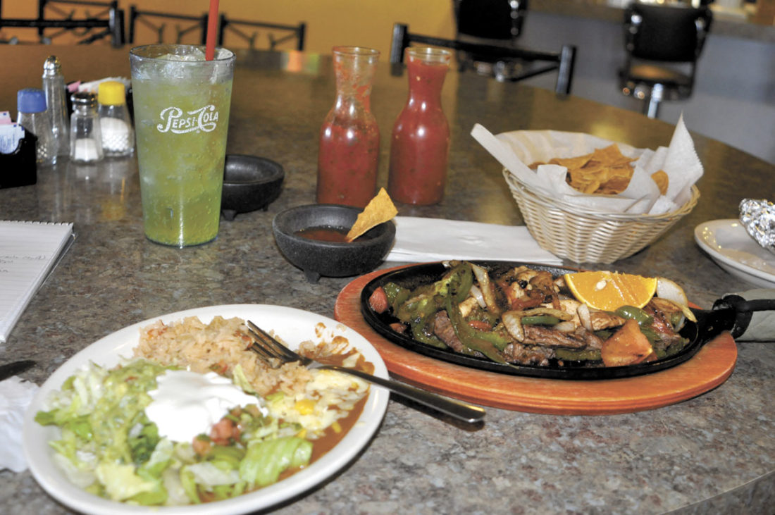-Messenger photo by Chad Thompson  A spread featuring chips and salsa, salad and the main course, chicken and steak fajitas, is shown here.