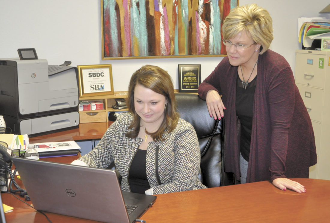 -Messenger photo by Peter Kaspari Stefanie Koenig, regional director of the North Central Iowa Small Business Development Center, left, works on her computer as Business Counselor Kimberly Tiefenthaler looks on.