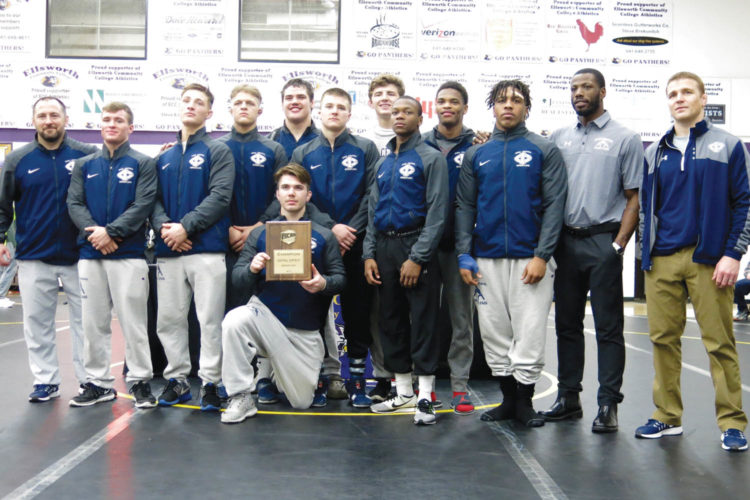 —Photo by Paul DeCoursey  The Iowa Central wrestling team stands with their trophy after winning the regional championship in Iowa Falls. The Tritons quailfied all ten wrestlers for nationals.