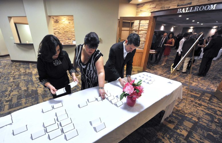 -Messenger photo by Hans Madsen  Board members Deb Johnson, left, and Darcy Lee help set up the place cards with a little help from Matt Johnson, right, during 19th annual Webster County Sweetheart Gala at the Best Western Startlite Village Inn & Suites Saturday evening.