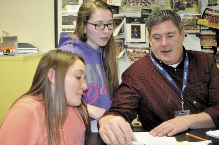 -Messenger photo by Chad Thompson  Monty Harker, high school biology teacher, gives instruction on Punnett squares to sophomores Jade LaRue, center, and Payton Reider at Clarion-Goldfield-Dows High School.