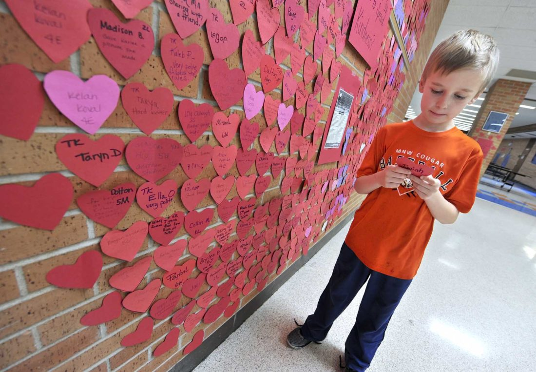 -Messenger photo by Hans Madsen  Isaiah Daggett, 8, a second-grade student at the Manson Northwest Elementary School in Barnum, looks over the heart he earned that's part of the Wall of Hearts Kindness Challange. Since Feb. 1, students at the school have nearly filled the entire floor to ceiling heart with their acts of kindness.