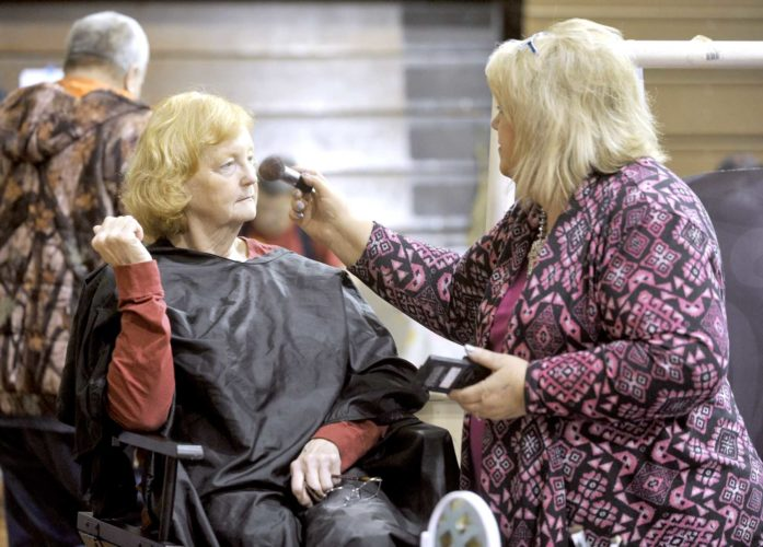 -Messenger photo by Hans Madsen  Judy Eslick, of Dayton, gets a makeover from Jane Klingson, owner of Jane's Hair Flair in Harcourt, who was exhibiting Younique makeup and skin care products at the Dayton Expo Saturday in the Dayton Community Center. The event highlights businesses in Dayton and the surrounding area.