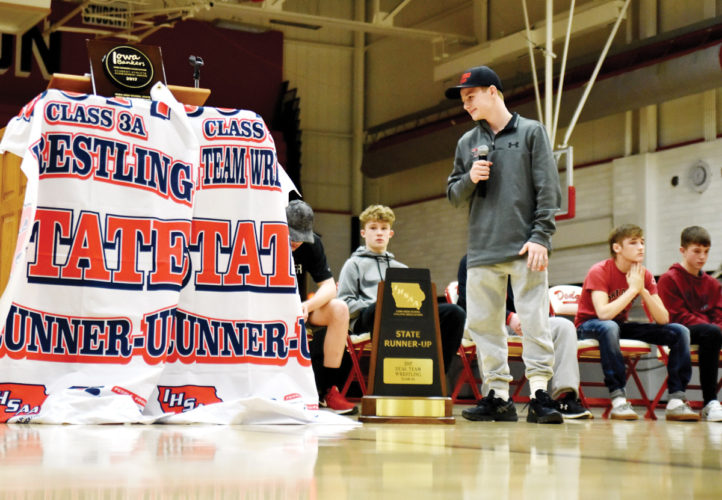 Messenger photo by Britt Kudla  Fort Dodge's Brody Teske, the first three-time state wrestling champion in school history, speaks next to the program's two new state runner-up banners and trophies during Sunday's welcome-home rally at the Dodger gym. For more photos, please visit CU.messengernews.net