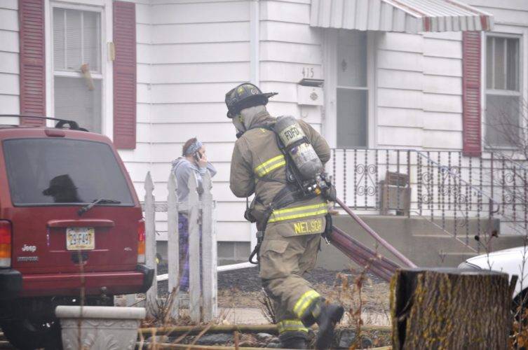 -Messenger photo by Peter Kaspari  Fort Dodge Firefighter Greg Nelson carries a fire hose into a burning home at 417 10th Ave. N. Monday afternoon.