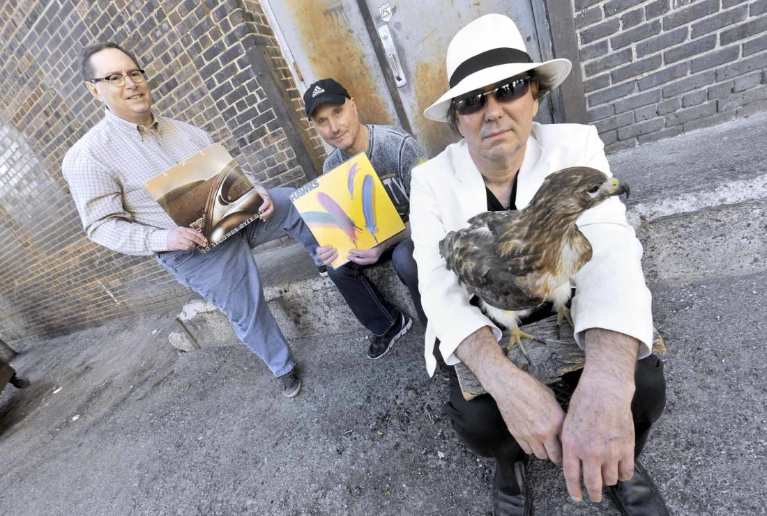 -Messenger photo by Hans Madsen  Above: Three members of the HAWKS, including Frank Wiewel, holding the taxidermied red tail hawk, along with Dave Hearn, at left, and Kirk Kaufman, holding two of the group's albums, pose recently in downtown Fort Dodge. The HAWKS are one of this year's featured warmup bands for the Shellabration featuring Huey Lewis & the News. The other warmup band is the group Far From Innocent. Two other original members of the HAWKS, Dave Steen and Larry Adams, will be joining the group for the concert. Avian hawk courtesy of Webster County Conservation.