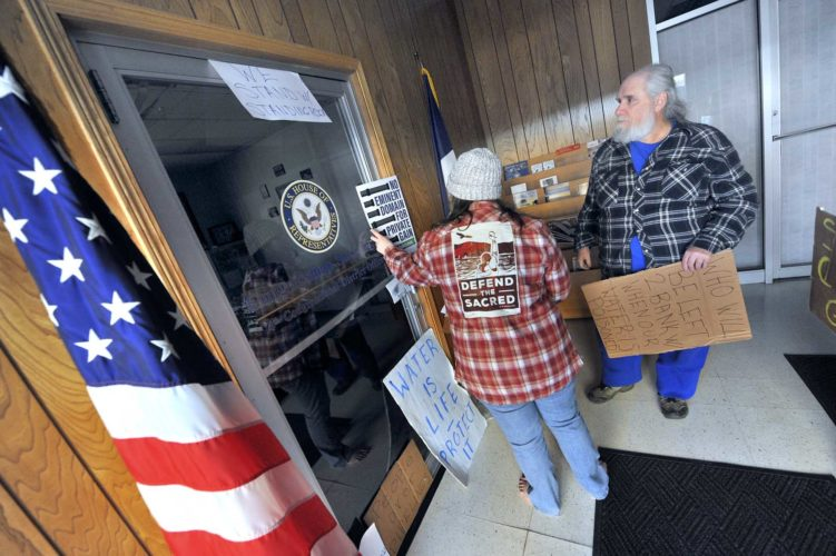 -Messenger photo by Hans Madsen  Dakota Access Pipe Line protesters Emma Schmit, of Rockwell City, along with Vince Wilson, of Pomeroy, leave some of their protest signs on the door to U.S. Rep. Steve King's office in downtown Fort Dodge Wednesday afternoon. With the office closed, the group was not able to engage in a planned sit-in.
