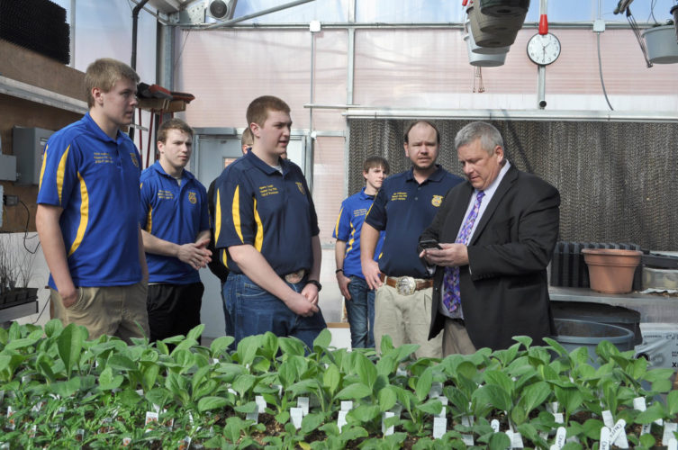 -Messenger photo by Adri Sietstra Iowa Secretary of Agriculture Bill Northey takes a picture of the plants growing inside the Webster City High School greenhouse on Tuesday afternoon. Members of the WCHS FFA along with WCHS FFA Advisor/Agriculture Instructor Kurt Veldhuizen gave Northey a tour of the greenhouse. Northey visited WCHS on Tuesday for National FFA Week and visited with FFA students about how they used the greenhouse for their classes.