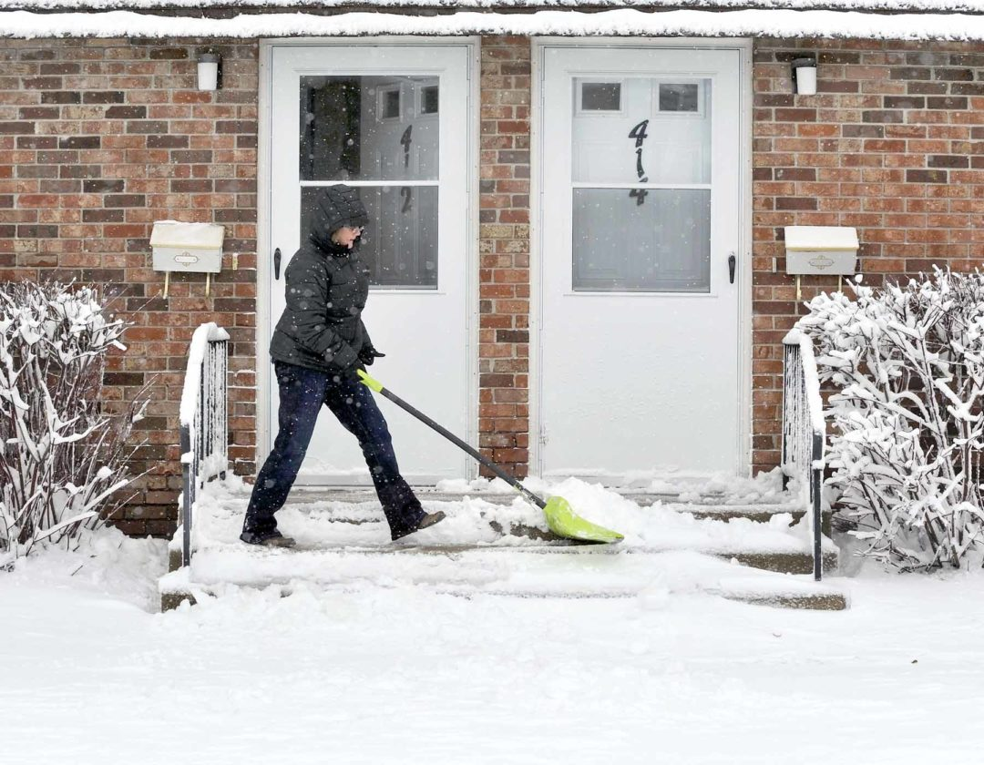 -Messenger photo by Hans Madsen  Rhonda Williams, of Fort Dodge, works on clearing her front steps Friday during her lunch hour to make her mail carrier's job a little easier in the 400 block of North 27th Street.