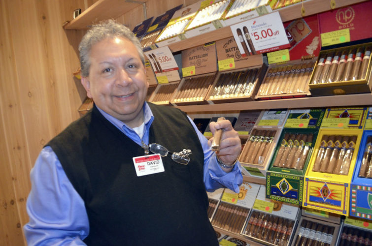 -Messenger photo by Joe Sutter  Store Leader David Munoz knows his cigars, and can help customers of any level of smoking experience pick out a cigar to their taste pick one out of the walk-in Humidor at the Kwik Star Express, now open at Second Avenue North and 15th Street.