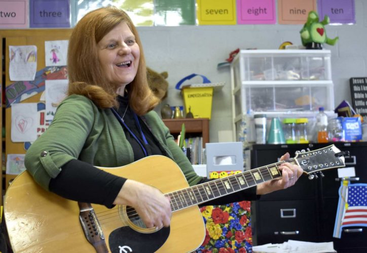 -Messenger photo by Chad Thompson  Jennifer Schild, a kindergarten teacher at Community Christian School in Fort Dodge, strums her guitar during a sing-along with her students recently. Schild started playing the guitar while attending the University of Northern Iowa in the late 1970s.