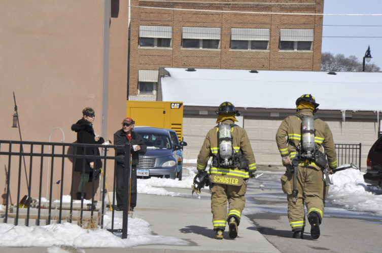 -Messenger photo by Peter Kaspari  Fort Dodge Firefighters Devon Schuster, left, and Randy Schilling prepare to enter the Heartland Senior Living apartments, 610 Central Ave., following a report of smoke Monday morning.