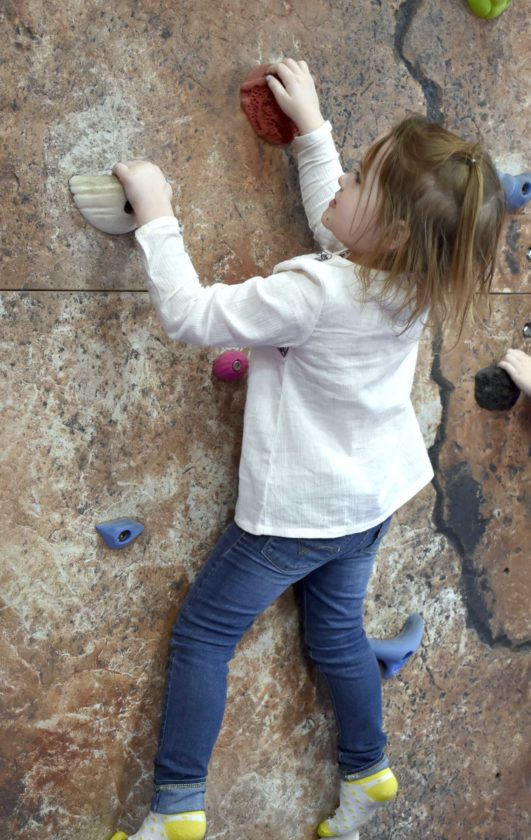 -Messenger photo by Chad Thompson  Rowan Enockson, 3, makes her way up the rock climbing wall at the Gilmore City-Bradgate Child Care Center recently.