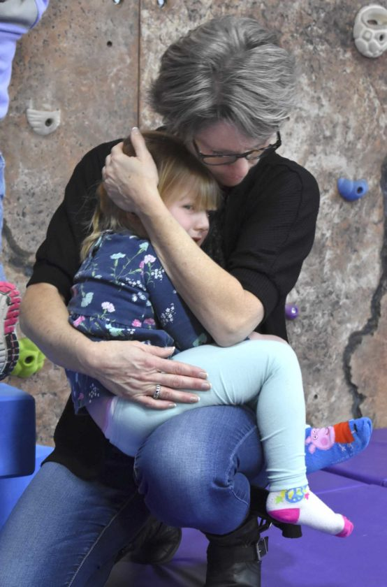 -Messenger photo by Chad Thompson  Wendy Herzberg, director of the Gilmore City-Bradgate Child Care Center, comforts Erika Lynch, 3, during play time at the day care facility recently.