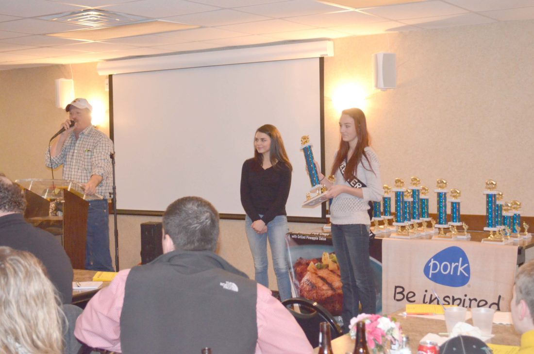 -Messenger photo by Kriss Nelson Scott Klingson called Monday night's trophy auction while Webster County Pork Queens Tielyr Clabaugh and Micaela Fevold assisted.