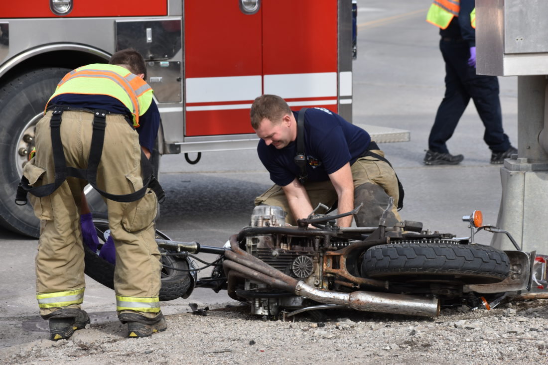 -Messenger photo by Chad Thompson Tom Ubben, Fort Dodge firefighter, prepares to remove a motorcycle from North 15th Street Sunday afternoon after it was involved in a car versus motorcycle crash. One man was seriously injured in the crash.