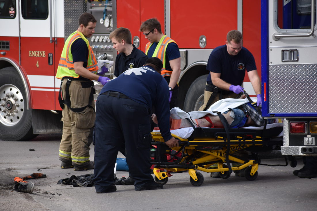 -Messenger photo by Chad Thompson   Fort Dodge paramedics and firefighters tend to Raymond Caquelin, 64, of Fort Dodge, after he was seriously injured in a motorcycle versus car crash Sunday afternoon.