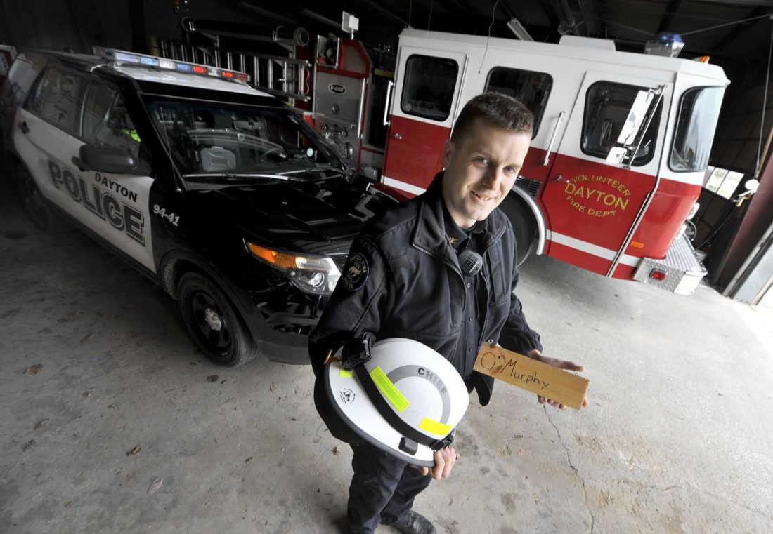 -Messenger photo by Hans Madsen  Dayton Police Chief, and also Dayton Fire Chief, Nick Dunbar, holds his helmet along with the name tag from Colin Murphy's turnout gear locker recently in the Dayton fire station. Dunbar serves in both capacities and is also a member of the Dayton Rescue Squad. Murphy, who drowned on June 19, 2016, was a Dayton firefighter and the sign will become part of a planned memorial to his memory inside the station.